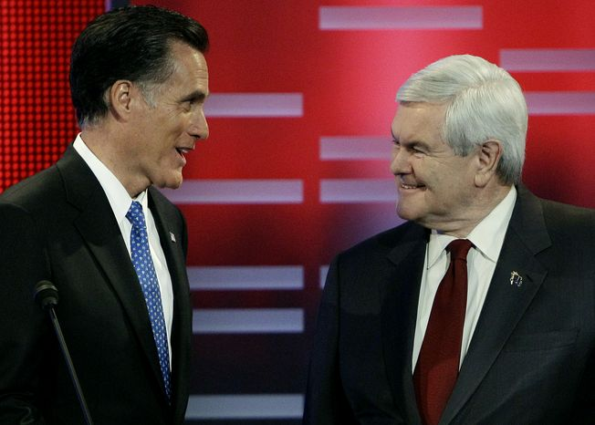 Former Massachusetts Gov. Mitt Romney (left) and former House Speaker Newt Gingrich talk during a break in the Republican presidential debate on Dec. 10, 2011, in Des Moines, Iowa. (Associated Press)