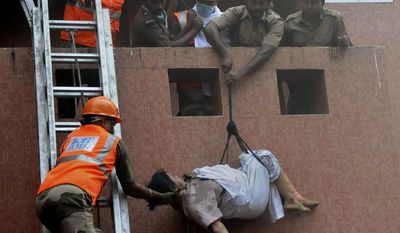 Rescue workers use ropes to evacuate people after a fire engulfed the Advanced Medical Research Institute hospital in Kolkata on Friday, Dec. 9, 2011. (AP Photo)