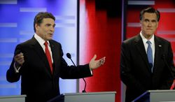 Texas Gov. Rick Perry (left) and former Massachusetts Gov. Mitt Romney take part in the Republican presidential debate on Saturday, Dec. 10, 2011, in Des Moines, Iowa. (AP Photo/Charlie Neibergall)
