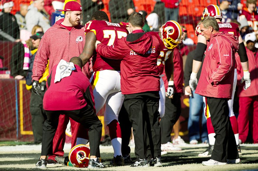 Washington Redskins head coach Mike Shanahan, right, looks on as Washington Redskins tackle Jammal Brown (77) appears to go down with an injury during warm ups and was taken back to the locker room before the Washington Redskins takes on the New England Patriots. (Andrew Harnik / The Washington Times)