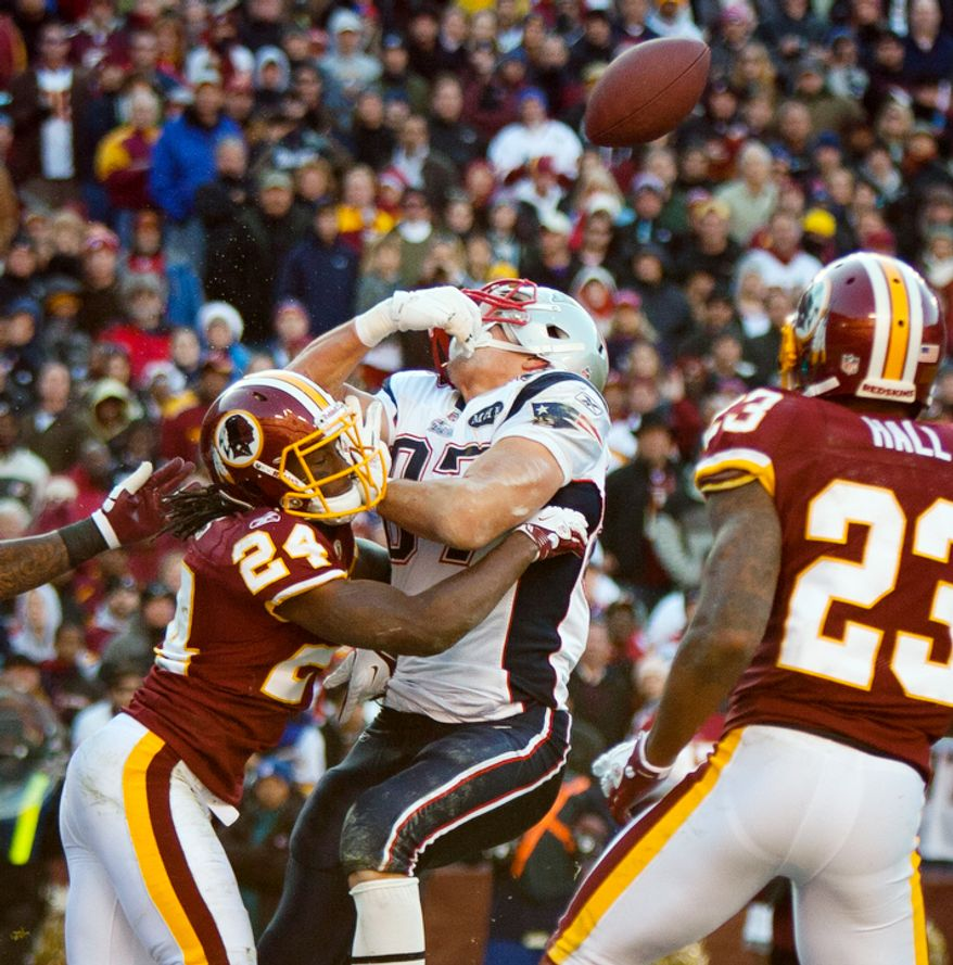 Washington Redskins strong safety DeJon Gomes (24) breaks up a pass in the end zone intended for New England Patriots tight end Rob Gronkowski (87) during the second quarter. (Pratik Shah/The Washington Times)