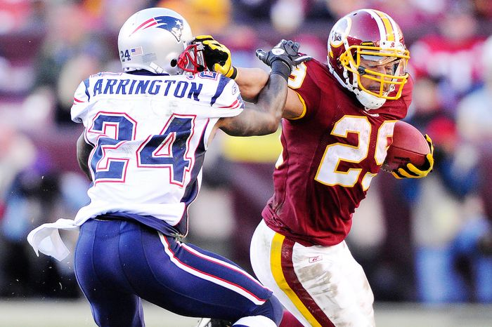 Washington Redskins running back Roy Helu (29) pushes off of New England Patriots cornerback Kyle Arrington (24) during an 8-yard run in the third quarter. Helu finished with 126 yards on the ground. giving him his third straight 100