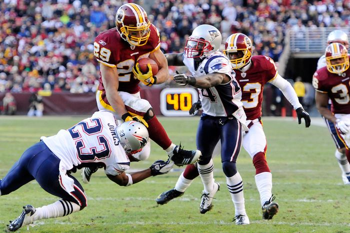 Washington Redskins running back Roy Helu (29) is brought down by New England Patriots defensive back Nate Jones (23) and cornerback Kyle Arrington (24) after gaining 12 yards in the third quarter. (Preston Keres/Special to The Washington Times)