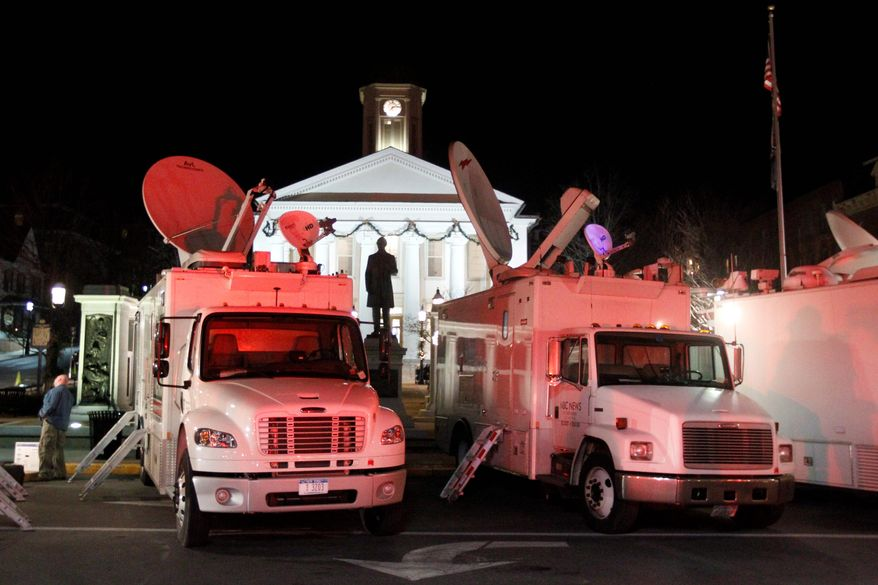 News trucks line the street in front of the Centre County Courthouse on Monday, Dec. 12, 2011, in Bellefonte, Pa. Former Penn State assistant football coach Jerry Sandusky, charged with more than 50 counts of child sex abuse, is scheduled to have a preliminary hearing at the courthouse on Tuesday. An order posted Monday says reporters will be allowed to email, send text messages and tweet from their laptop computers and handheld devices from inside the courtroom in Centre County during the hearing. (AP Photo/Matt Rourke)