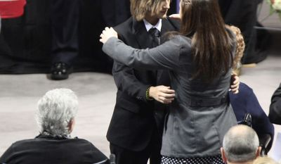 The family of Officer Deriek W. Crouse embraces during his memorial service Monday in Blacksburg, Va. (Associated Press)
