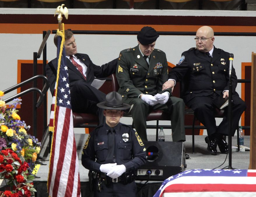 Virginia Gov. Bob McDonnell (left) and the Rev. Tommy McDearis (right) comfort Army Sgt. Paul Sweeney during the memorial service Monday in Blacksburg for Deriek W. Crouse, a Virginia Tech police officer who was fatally shot last week. (Associated Press)