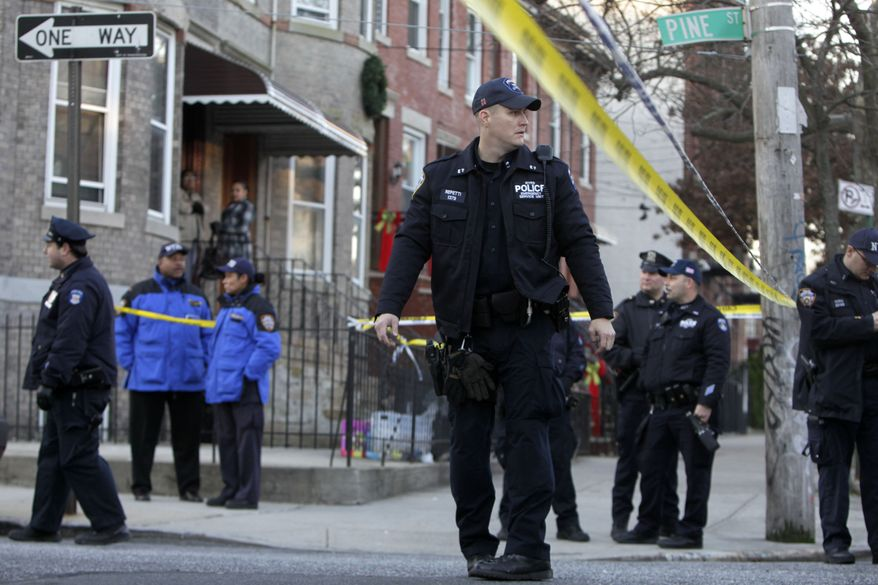 Police officers stand near a crime scene where a fellow officer was shot in the Cypress Hills section of the Brooklyn borough of New York on Monday, Dec. 12, 2011. (AP Photo/Seth Wenig)
