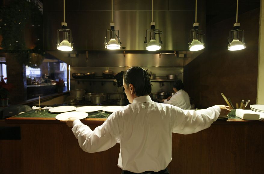 Workers prepare for lunch Dec. 7, 2011, in the kitchen at the Palio D'Asti restaurant in San Francisco. (Associated Press)