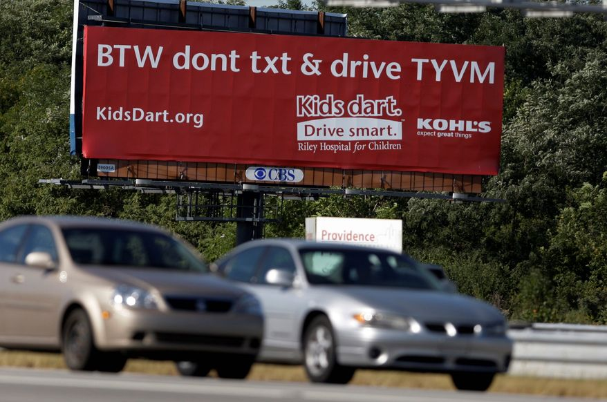 **FILE** Motorists pass a billboard encouraging people not to text while driving in Indianapolis. (Associated Press)