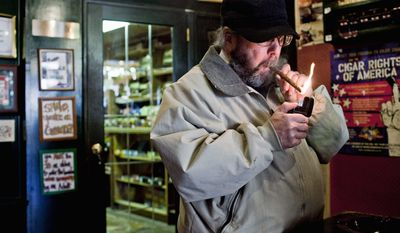 Peter Finkelstein of Annapolis lights a cigar at the Annapolis Cigar Co. A campaign is under way for the General Assembly to raise taxes on cigars and chewing tobacco to deter teens who use them as alternatives to more expensive cigarettes. (T.J. Kirkpatrick / The Washington Times)