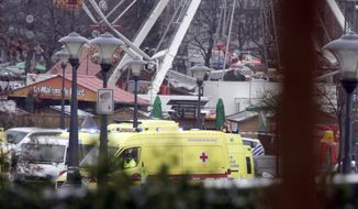 Ambulances are seen near a Christmas market in Liege, Belgium, on Tuesday, Dec. 13, 2011, after several men attacked a crowd in a busy square with hand grenades and gunfire. (AP Photo/Virginia Mayo)