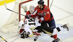Washington Capitals defenseman John Carlson (74) shoves Pittsburgh Penguins left wing James Neal during the second period of an hockey game, Thursday, Dec. 1, 2011, in Washington. (AP Photo/Nick Wass)