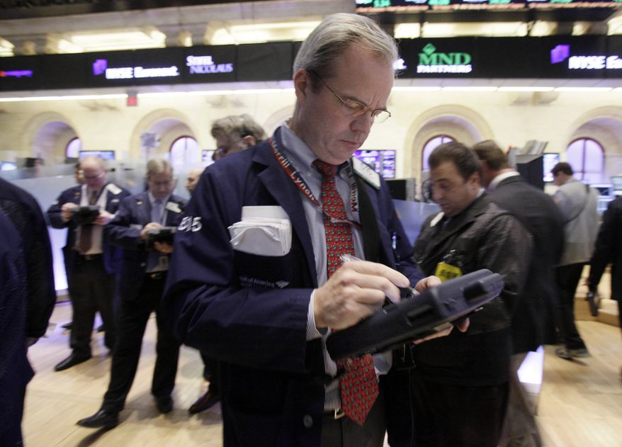 Trader David O'Day (center) works on the floor of the New York Stock Exchange on Tuesday, Dec. 13, 2011. (Associated Press)