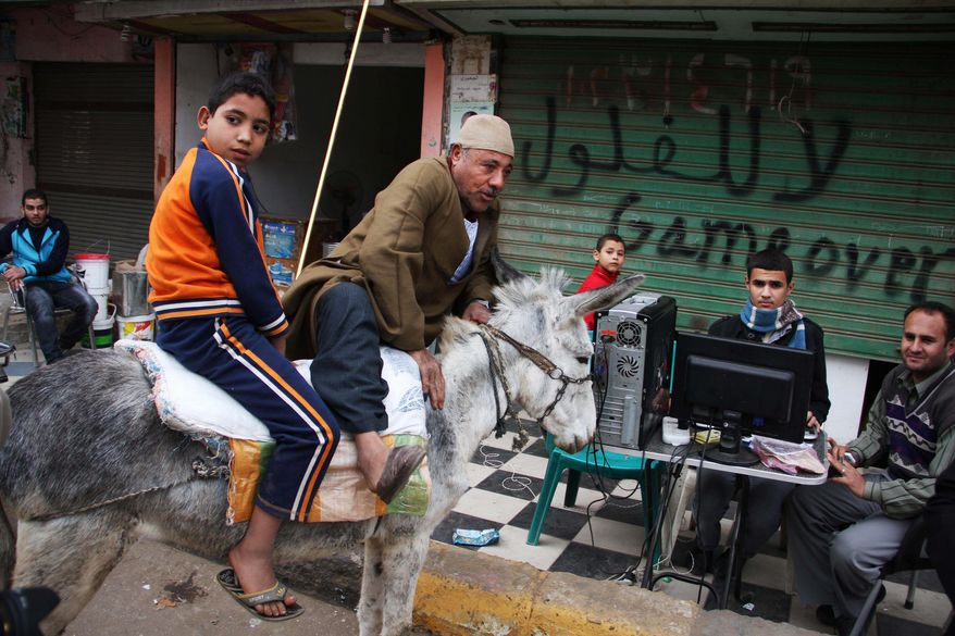"""An Egyptian man rode his donkey to a polling station in Menoufia, Egypt, as large numbers turned out Wednesday for the second round of parliamentary elections. Writing on the wall reads """"no to reminiscence of the old regime."""" (Associated Press)"""