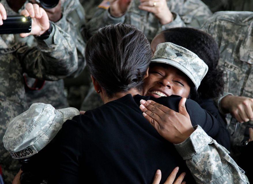 "First lady Michelle Obama welcomes a servicewoman in a maintenance hangar at Fort Bragg, N.C., on Wednesday. She told returnees that the president kept his promise ""to responsibly bring you home from Iraq."" (Associated Press)"