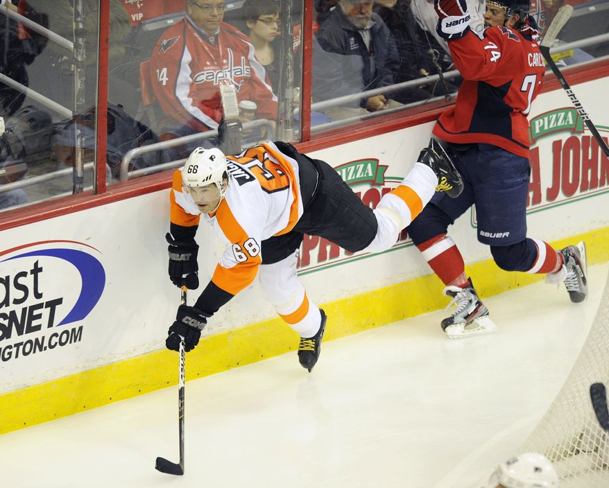 Philadelphia Flyers right wing Jaromir Jagr (68), of the Czech Republic, gets tripped up by Washington Capitals defenseman John Carlson (74) during the second period of an NHL hockey game, Tuesday, Dec. 13, 2011, in Washington. (AP Photo/Nick Wass)
