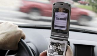 ** FILE ** A driver in Brunswick, Maine, holds a cellphone on Sept. 20, 2011. (AP Photo/Pat Wellenbach)