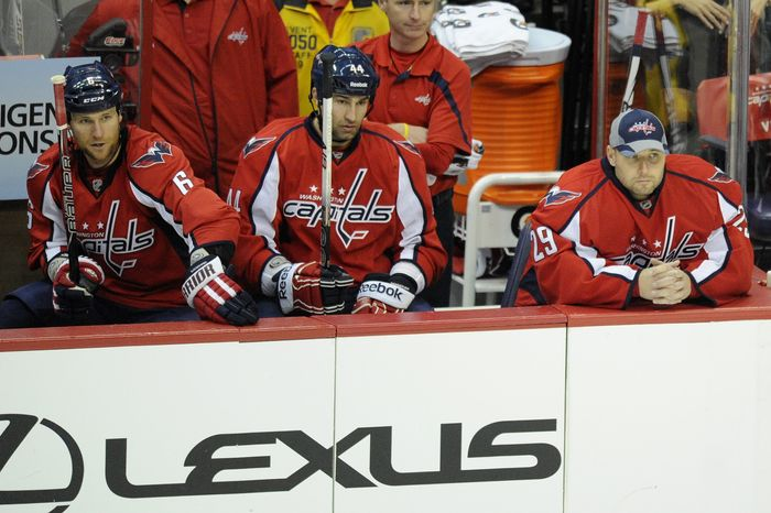 Washington Capitals' Dennis Wideman, left, Roman Hamrlik, center, of the Czech Republic, and goalie Tomas Vokoun, right, of the Czech Republic, look on during the third period of an NHL hockey game against the Philadelphia Flyers, Tuesday, Dec. 13, 2011, in Washington. Vokoun was pulled after the second period after giving up four goals as the Flyers won 5-1. (AP Photo/Nick Wass)