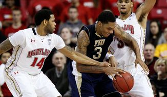 Maryland forward Ashton Pankey, guarding Florida International's Dominique Ferguson on Wednesday along with teammate Sean Mosley (14), played through a split lip to notch 13 points and six rebounds in the Terps' 65-61 win. (Associated Press)
