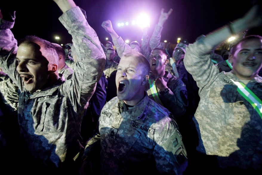 HOMEWARD BOUND: Soldiers with the 1st Cavalry Division show appreciation for the band Filter as they relax Thursday at Camp Virginia, Kuwait, where they await deployment home after leaving Iraq. (Associated Press)