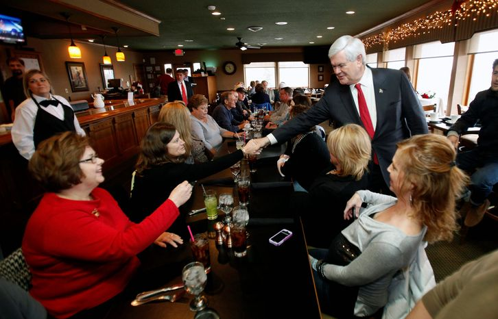 Republican presidential candidate Newt Gingrich greets potential voters Thursday at the Willow Ridge Golf Course in Fort Dodge, Iowa. He vowed to run a positive campaign,, less than three weeks before the GOP caucuses in a state where his once-strong support has slipped recently. (Associated Press)