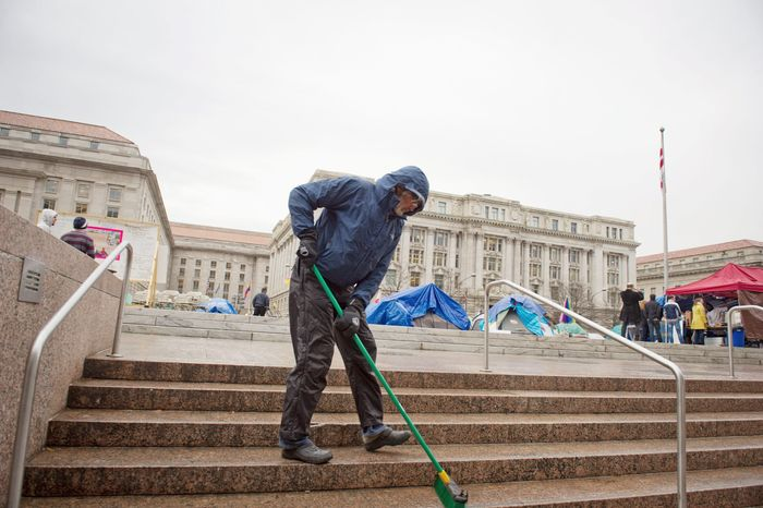 With the John A. Wilson Building looming in the distance, Charles Holsopple helps keep the area clean at the Stop the Machine protest encampment at Freedom Plaza in Washington on Thursday. Mr. Holsopple, 58, left his home in Tampa Bay, Fla., to join the movement and has been here since Oct. 6. (Rod Lamkey Jr./The Washington Times)