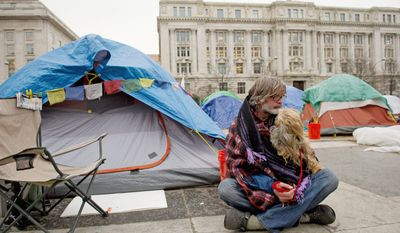 Charles Holsopple spends time with his dog, Rocko Bhakti, outside of his tent at the Stop the Machine protest encampment at Freedom Plaza in Washington on Thursday. Mr. Holsopple, 58, left his home in Tampa Bay, Fla., to join the movement and has been here since Oct. 6. (Rod Lamkey Jr./The Washington Times)