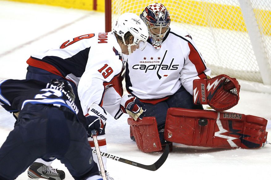Washington Capitals goaltender Michal Neuvirth (30) and Nicklas Backstrom (19) stop Winnipeg Jets forward Chris Thorburn (22) during the second period of an NHL hockey game in Winnipeg on Thursday, Dec. 15, 2011. (AP Photo/The Canadian Press, John Woods)