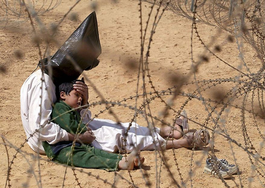"In this March 31, 2003 file photo, an Iraqi prisoner of war comforts his 4-year-old son at a regrouping center for POWs captured by the U.S. Army 101st Airborne Division near An Najaf, Iraq. The man was seized in An Najaf with his son, and the U.S. military did not want to separate father and son. In the beginning, it all looked simple: topple Saddam Hussein, destroy his purported weapons of mass destruction and lay the foundation for a pro-Western government in the heart of the Arab world. Nearly 4,500 American and more than 100,000 Iraqi lives later, the objective now is simply to get out _ and leave behind a country where democracy has at least a chance, where Iran does not dominate and where conditions may not be good but ""good enough."" (AP Photo/Jean-Marc Bouju, File)"