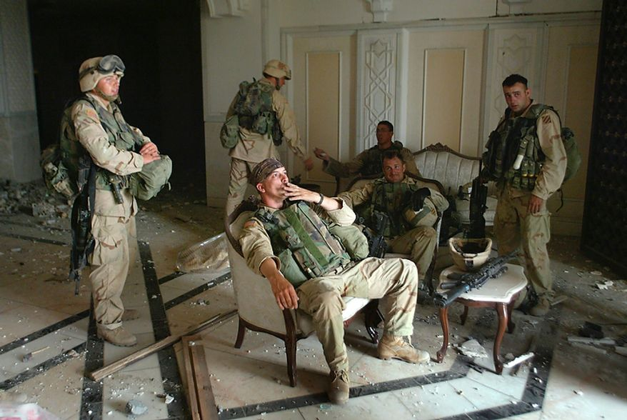 """In this April 7, 2003 file photo, U.S. Army Staff Sgt. Chad Touchett, center, relaxes with comrades from A Company, 3rd Battalion, 7th Infantry Regiment,  following a search in one of Saddam Hussein's palaces damaged after a bombing, in Baghdad. In the beginning, it all looked simple: topple Saddam Hussein, destroy his purported weapons of mass destruction and lay the foundation for a pro-Western government in the heart of the Arab world. Nearly 4,500 American and more than 100,000 Iraqi lives later, the objective now is simply to get out _ and leave behind a country where democracy has at least a chance, where Iran does not dominate and where conditions may not be good but """"good enough."""" (AP Photo/John Moore, File)"""