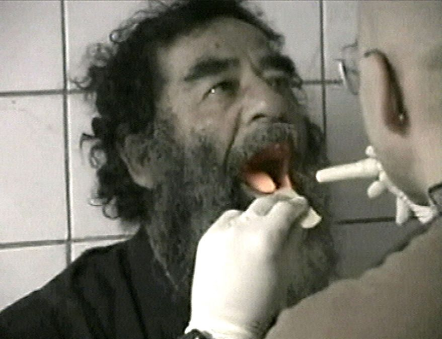 "In this  Dec. 14, 2003 file image taken from video, captured former Iraqi leader Saddam Hussein undergoes medical examinations in Baghdad. In the beginning, it all looked simple: topple Saddam Hussein, destroy his purported weapons of mass destruction and lay the foundation for a pro-Western government in the heart of the Arab world. Nearly 4,500 American and more than 100,000 Iraqi lives later, the objective now is simply to get out _ and leave behind a country where democracy has at least a chance, where Iran does not dominate and where conditions may not be good but ""good enough.""   (AP Photo/US Military via APTN, File)"