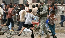 """In this May 28, 2007 file photo, a young boy seeks shelter behind a soldier with the U.S. Army's 82nd Airborne division after gunshots rang out at the scene where just a few minutes earlier a suicide car bomber blew himself up in a busy commercial district in central Baghdad. killing at least 21 people and wounding 66. In the beginning, it all looked simple: topple Saddam Hussein, destroy his purported weapons of mass destruction and lay the foundation for a pro-Western government in the heart of the Arab world. Nearly 4,500 American and more than 100,000 Iraqi lives later, the objective now is simply to get out _ and leave behind a country where democracy has at least a chance, where Iran does not dominate and where conditions may not be good but """"good enough."""" (AP Photo/Khalid Mohammed, File)"""