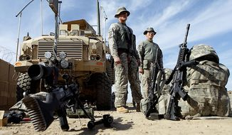 ** FILE ** U.S. Army soldiers with 1st Brigade, 1st Cavalry Division stand near their armored vehicles before they start their journey home at Contingency Operating Site Kalsu, about 55 kilometers (35 miles) south of Baghdad, Iraq on Monday, Dec. 5, 2011. (AP Photo/Khalid Mohammed)