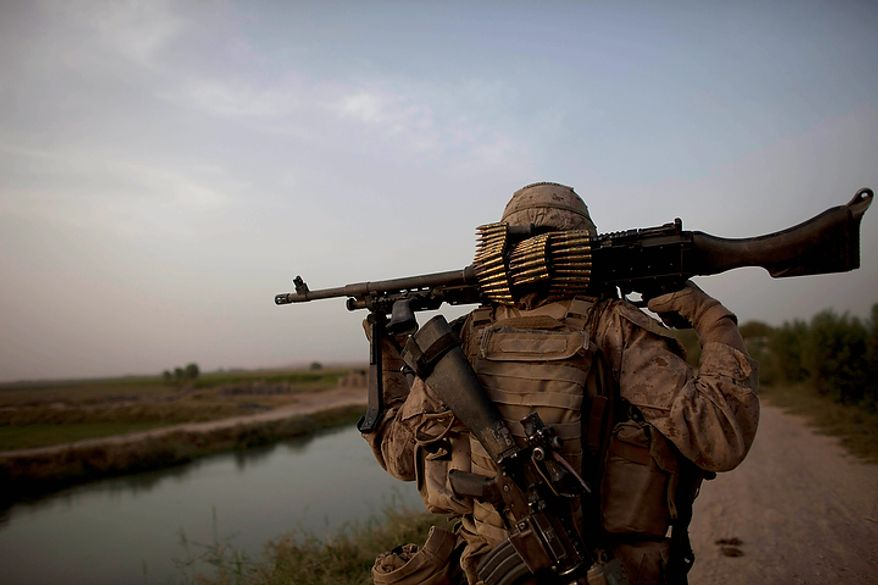 """In this Aug. 25, 2011, file photo U.S. Marine Lance Cpl. Lane Edward Morrow,of Susanville, Calif., of the 3rd Platoon, Kilo Company, 3/4 Marines, guards a vehicle checkpoint in early morning in Helmand province, southern Afghanistan. """"We need to get back to our bread and butter"""" Marine Corps commandant, Gen. James F. Amos, told Marines Nov. 23 at Camp Lawton, a U.S. special operations base in Afghanistan's Herat province. That begins, he said, with moves such as returning to a pattern of continuous rotations of Marines to the Japanese island of Okinawa, home of the 3rd Marine Division formed in the early days of World War II. (AP Photo/Brennan Linsley, File)"""