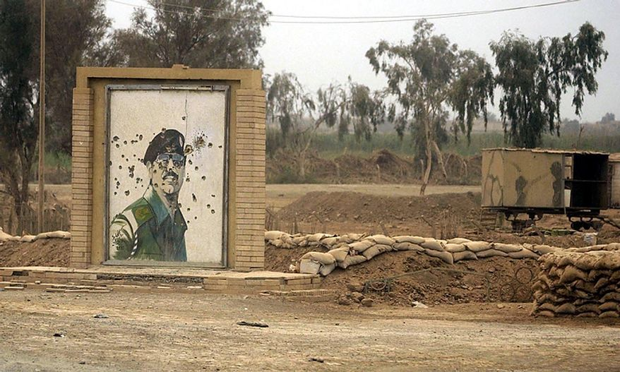 A portrait of Saddam Hussein riddled with bullet holes near Baghdad in central Iraq, Monday, April 7, 2003. ( J.M. Eddins Jr. / The Washington Times )