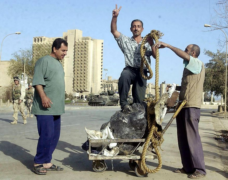 An Iraqi man stands on the head of a statue of Saddam Hussein as US Marines occupy the center of Baghdad, Iraq. Pockets of resistence remain in the northern part of the city and sniper fire can be heard everywhere. Thursday, April 10, 2003. ( J.M. Eddins Jr. / The Washington Times )
