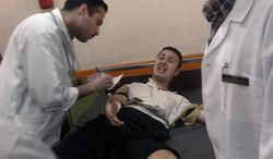 ** FILE ** Doctors in at a Red Crescent Hospital examine a man who was shot in the leg when caught in the crossfire between Iraqi factions in the Saddam City area of Baghdad, Iraq. The doctors said that they have not treated any war casualties in two days, but are flooded with victims of civil chaos and fighting and are running low on supplies, Friday, April 11, 2003. ( J.M. Eddins Jr./The Washington Times )