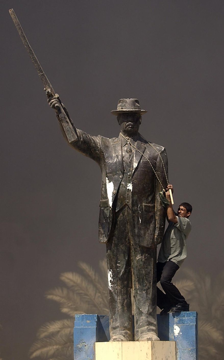 An Iraqi boy tries to pull down a statue of Saddam Hussein near burning government buildings in Baghdad, Iraq Friday, April 11, 2003. ( J.M. Eddins Jr. / The Washington Times )