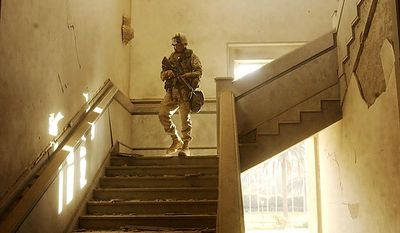 A US Marine walks through the rubble of the Iraqi Parliment Building in Saddam Hussein's Palace complex near the Tigris River Saturday, April 12, 2003. ( J.M. Eddins Jr. / The Washington Times )