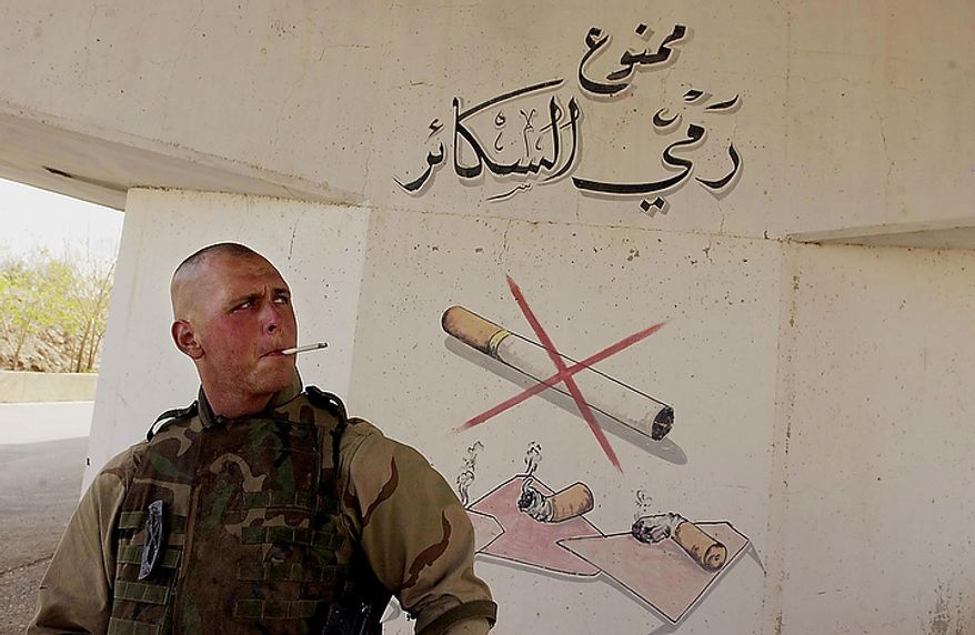 US Marine Lance Cpl. Jarrod Antczak smokes a cigarette under a no smoking sign at Saddam Hussein's palace complex in Tikrit in Northern Iraq Monday, April 14, 2003. ( J.M. Eddins Jr. / The Washington Times )