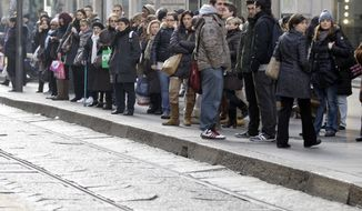 People wait Dec.15, 2011, at a tram station during a transport strike in Milan. (Associated Press)