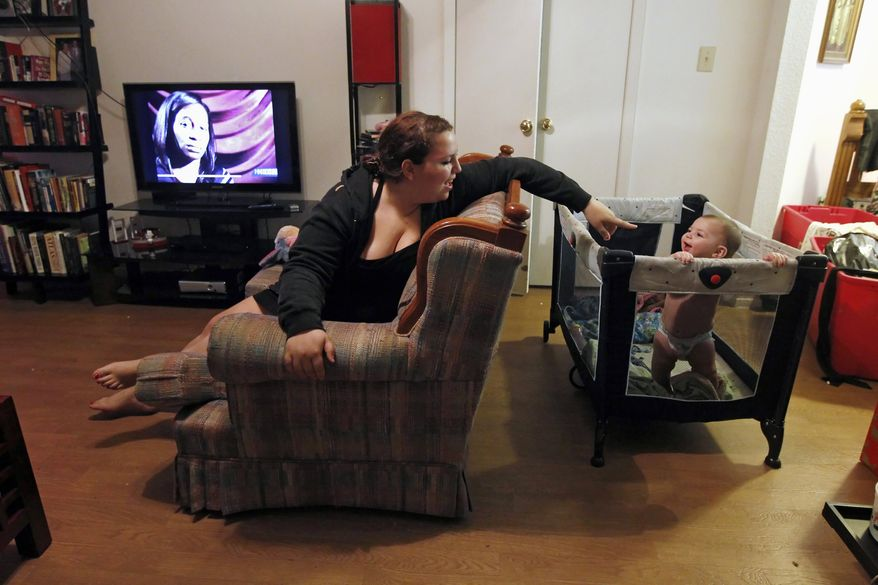 Zenobia Bechtol, 18, and her 7-month-old daughter, Cassandra, play in the living room of her mother's apartment in Austin, Texas, on Wednesday, Dec. 14, 2011, after she and her boyfriend were evicted from their apartment after he lost his job. (AP Photo/Erich Schlegel)
