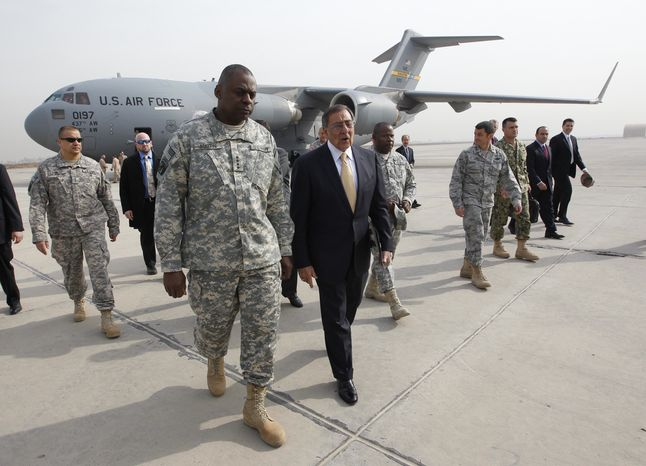 ** FILE ** Defense Secretary Leon E. Panetta (center right) walks across the apron with Army Gen. Lloyd J. Austin III (center left), commander of U.S. forces in Iraq, after arriving in Baghdad on Thursday, Dec. 15, 2011. Mr. Panetta was participating in ceremonies marking the end of the U.S. military mission in Iraq. (AP Photo/Pablo Martinez Monsivais, Pool)