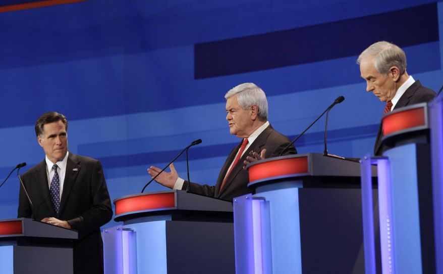 Republican presidential candidate and former House Speaker Newt Gingrich (center) speaks Dec. 15, 2011, as former Massachusetts Gov. Mitt Romney (left) and Texas Rep. Ron Paul listen during a Republican presidential debate in Sioux City, Iowa. (Associated Press)