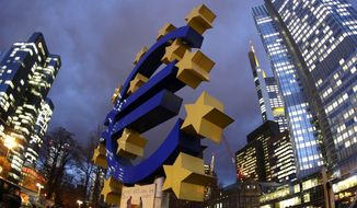 A euro sculpture stands in front of the European Central Bank (right) in Frankfurt, Germany. (Associated Press)
