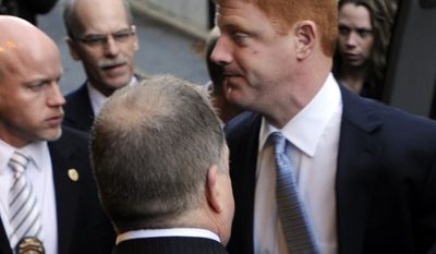 Penn State assistant football coach Mike McQueary (right) arrives Dec 16, 2011, for a preliminary hearing related to the Jerry Sandusky child sex abuse case at Dauphin County Court in Harrisburg, Pa., surrounded by heavy security. (Associated Press)