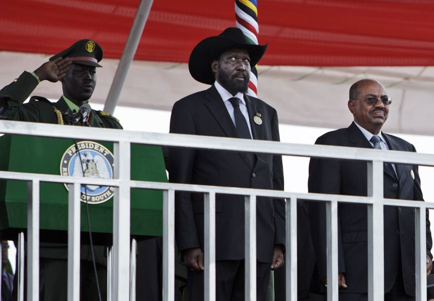 **FILE** South Sudan's President Salva Kiirr (center) and Sudan's President Omar al-Bashir (right) stand July 9, 2011, on the podium at the start of independence celebrations in Juba, South Sudan. South Sudan raised the flag of its new nation for the first time, as thousands of South Sudanese citizens swarmed the capital of Juba to celebrate the country's birth. (Associated Press)