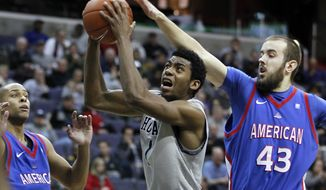 Georgetown's Hollis Thompson (1) looks for room around American's Charles Hinkle (23) and Mike Bersch (43) during the second half, Saturday, Dec. 17, 2011, in Washington. Thompson had 15 points and eight rebounds in Georgetown's 81-55 win. (AP Photo/Luis M. Alvarez)