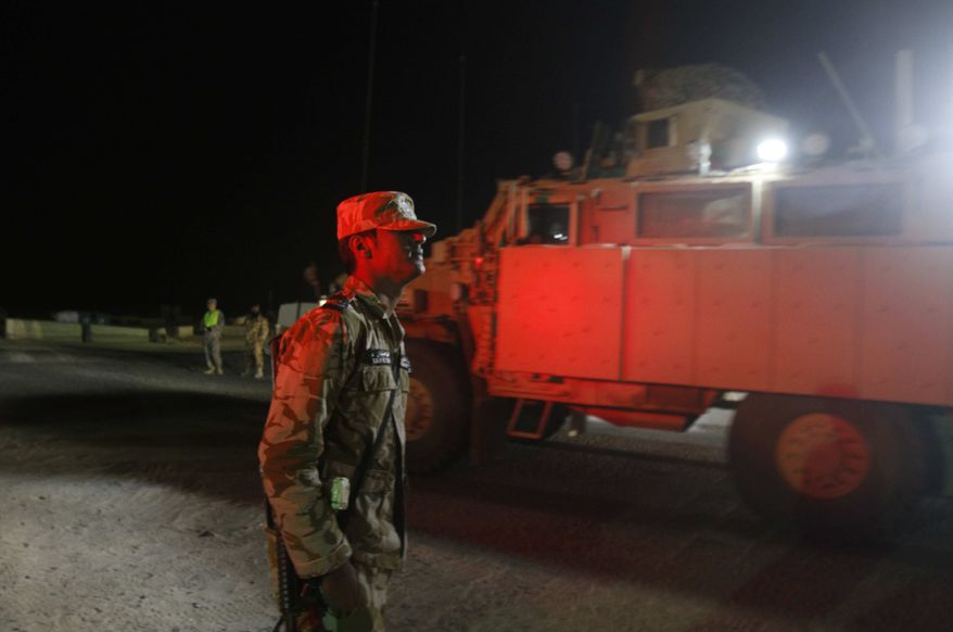 A Kuwaiti border guard watches a convoy from the U.S. Army's 3rd Brigade, 1st Cavalry Division crossing the border from Iraq into Kuwait, Sunday, Dec. 18, 2011. The brigade's special troops battalion are the last American soldiers to leave Iraq. The U.S. military says the last American troops have left Iraq as the nearly nine-year war ends. (AP Photo/Maya Alleruzzo)