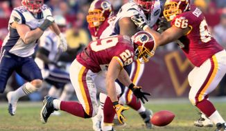 Running back Roy Helu chases down the ball after fumbling a handoff from Rex Grossman in the third quarter of an NFL football game Sunday Dec. 11, 2011, at FedEx Field in Landover, Md. (AP Photo/ The Free Lance-Star, Dave Ellis)